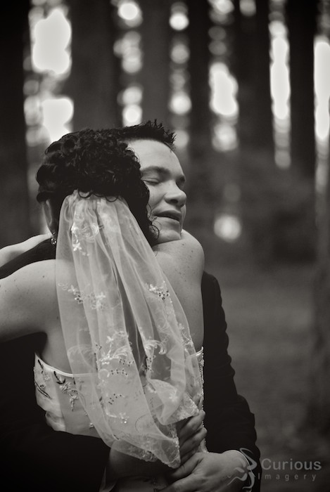 bride and groom embrace in forest, black and white, sentimental, hug, smiling, happy