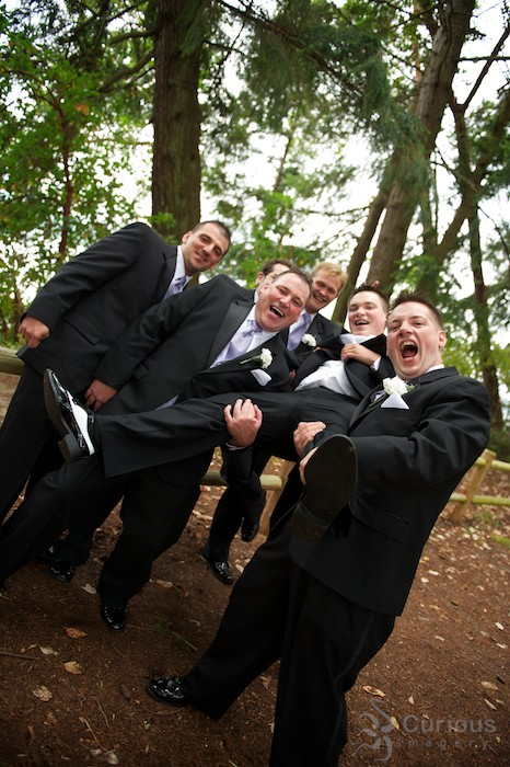 crazy groomsmen hold up groom. yelling and laughing, high energy wedding portrait