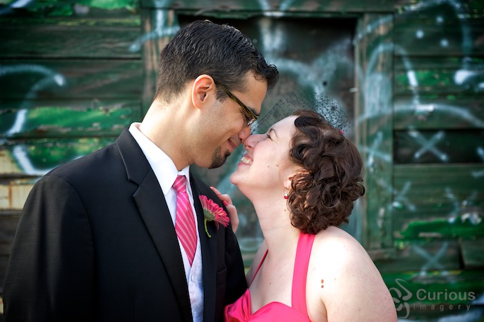 Quirky alternative bride and groom touch noses, graffiti behind.