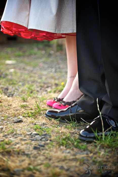 Detail of bride and groom's shoes. Pink heels and shiny black dress shoes.