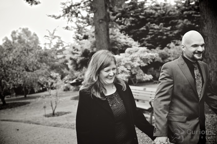 Low contrast black and white of happy bride and groom walking in garden