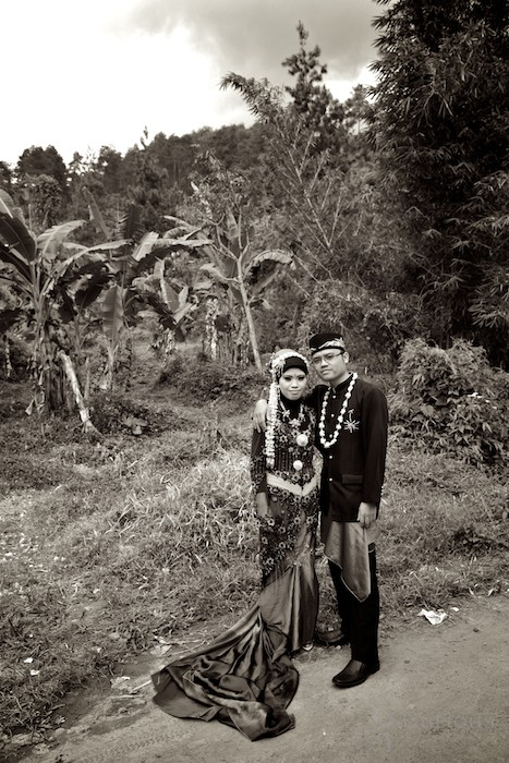 Indonesian bride and groom pose outside by banana trees