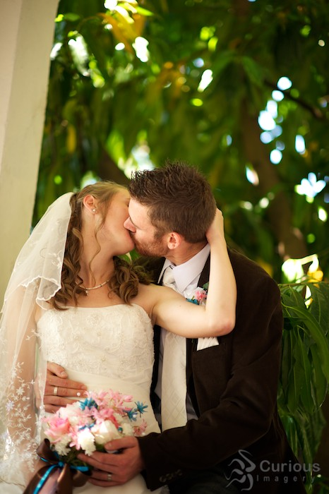 bride and groom kiss with green foliage behind