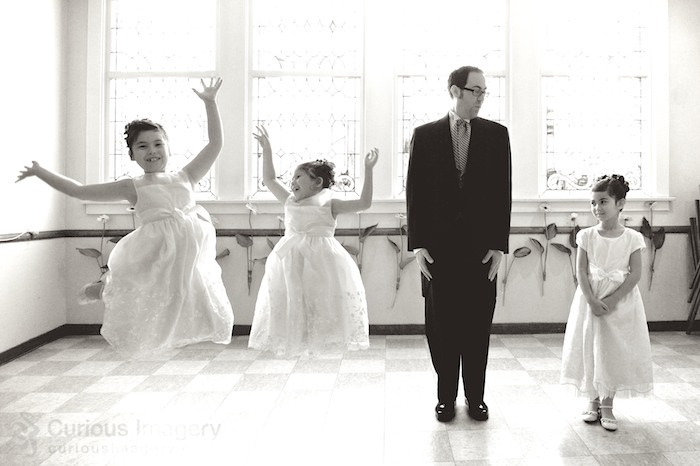 Goofy groom jumping with flower girls