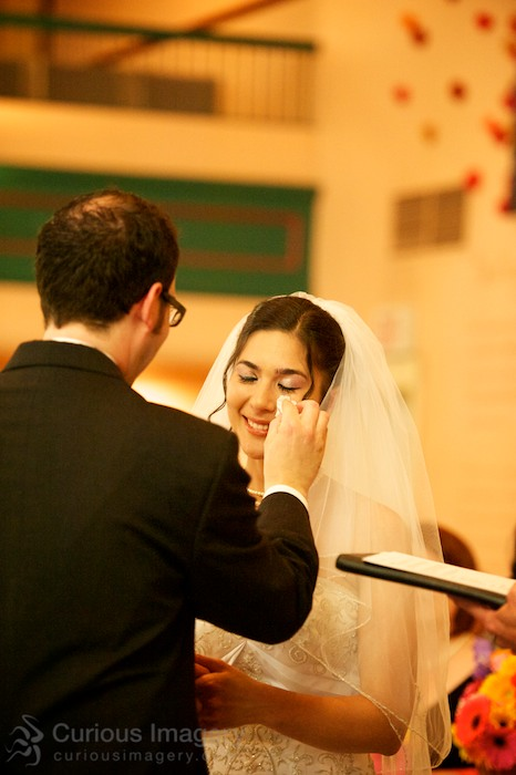 Groom wiping bride's tears in wedding ceremony