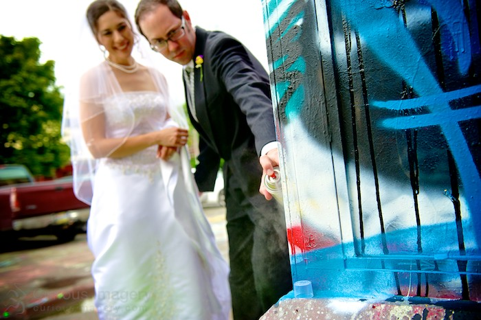 bride and groom tagging graffiti wall
