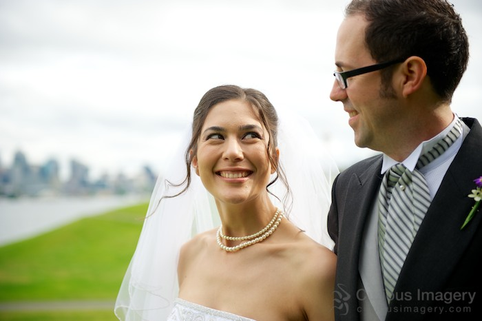 Bride smiling at groom with Seattle City Skyline behind