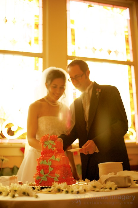 Bride and groom cutting wedding cake, with backlit stained glass