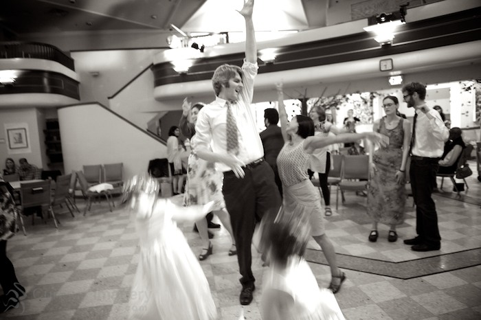 Guests dancing at wedding reception, black and white
