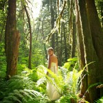 Bride in old growth forest, looking at camera.