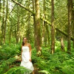 Smiling bride in old growth forest, looking at camera. Index, Washington.
